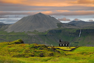 Iceland. Wooden church in the background of mountains and orange morning clouds