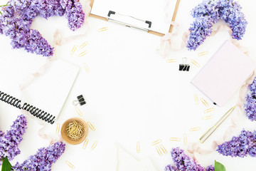 Blogger workspace with clipboard, dairy, envelope, lilac and accessories on white background. Flat lay, top view.