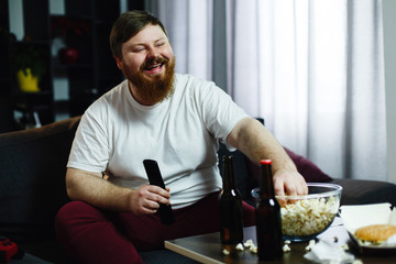 Happy fat man sits on the sofa and watches TV with popcorn and beer