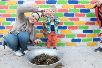 Happy mother shows crayfish caught in the river to two of their charming sons against the backdrop of multi-colored brick wall. Caucasian children and mom have a good time together.