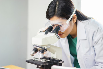 Female medical Doctor or research scientist looking through a microscope in a laboratory.science experiments,laboratory glassware containing chemical liquid for researching biology chemistry samples