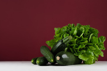 Green summer vegetables on white wood board and bordo kitchen wall. Modern elegant colorful concept kitchen interior.