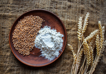 wheat flour and spikelets of wheat on sackcloth background
