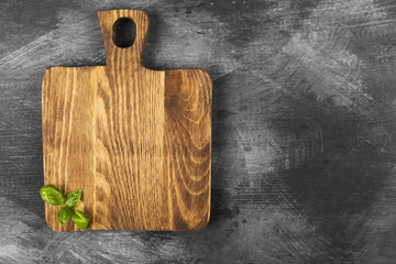 Wooden cutting board and leaves of basil on dark background. Top view, copy space. Food background