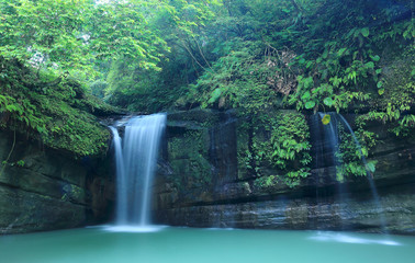 A cool refreshing waterfall tumbling down the cliff into an emerald pond hidden in a mysterious forest of lush greenery ~ Scenic view of a beautiful waterfall and intriguing river potholes in Taiwan