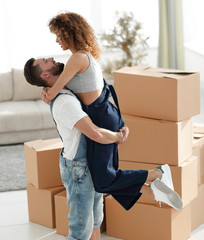 Hugging couple, against the background of boxes