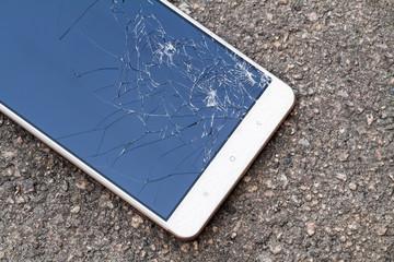 Smartphone with broken blue display screen is lying on the asphalt. Closeup, selective focus
