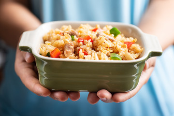Hand holding a bowl of fried rice, Thai cuisine
