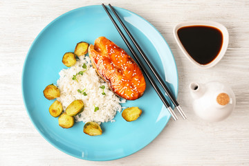 Fish steak served with rice and soy sauce on wooden background