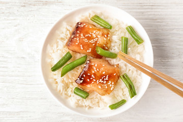Fish fillet served with rice and green beans on wooden background