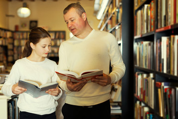 man with daughter looking for interesting books