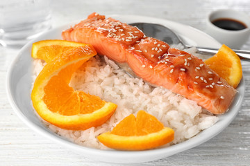 Fish fillet served with rice and orange slices in bowl