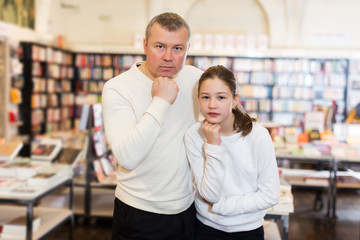 pensive man and preteen girl in bookstore