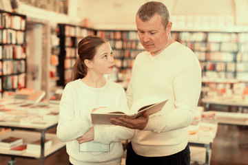 Cheerful girl with father choosing books