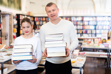 Portrait of tweenage girl with father standing in library with pile of books in hands