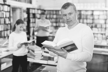Male reading books in bookshop