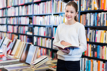 Intelligent preteen girl standing alone near bookcase in library browsing textbooks