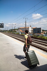 Man dragging luggage on wheels at train station