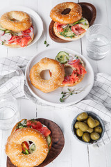 Bagels with salmon fish, cream cheese, cucumber and fresh radish slices on white wooden background