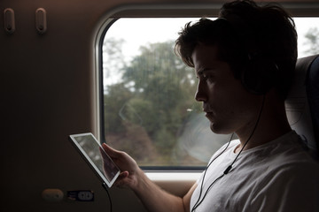 Man in train watching a movie with headphones