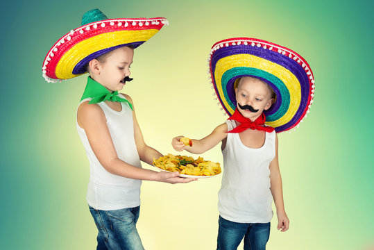 Two boys in a Mexican sombrero eat crispy chips.