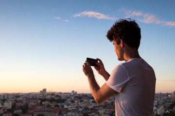 Man taking a photo of Lisbon skyline at dusk with mobile phone