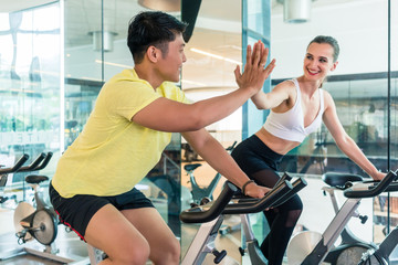 Cheerful young man and his beautiful workout partner and friend giving high five during indoor cycling workout in a trendy fitness club