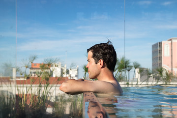 Young man on rooftop swimming pool