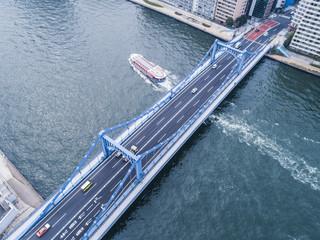 大きな橋をくぐる旅客船。都心の川。