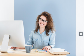 Cheerful European business woman in round spectacles, smiles happily sitting at office and studies business documents, looking and smiling at the camera during working day.