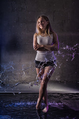 Girl in the white shirt with water drop in a dark room illuminated by light during a photoshoot with water