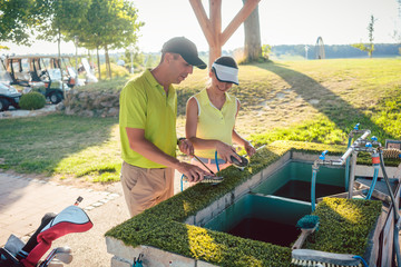 Happy couple or two best friends smiling while cleaning with brushes and water their clubs outdoors in a professional golf club with modern facilities