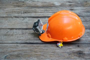 Orange safety helmet Installs a wireless video camera put on an old wooden floor.