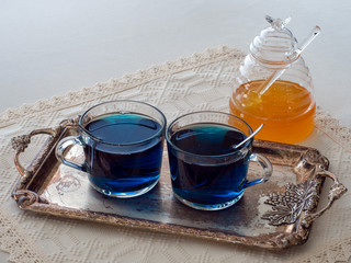Two cups of blue butterfly pea flower tea, set on a silver tray and a jar of honey