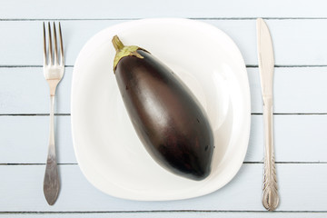 Ripe eggplant on white plate with cutlery. Top view on wooden table. Vegetarian food concept