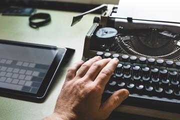 Man Hand On Old Typewriter And Digital Tablet. Journalism Report Concept
