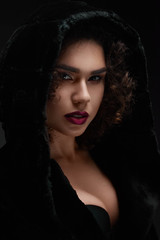 Sexy curly model wearing black hood looking at camera. Wearing black bra and jacket. Woman having light day make up and saturated violet make up. Black studio background.