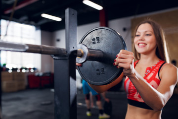 Photo of smiling sportswoman in sports clothes with barbell