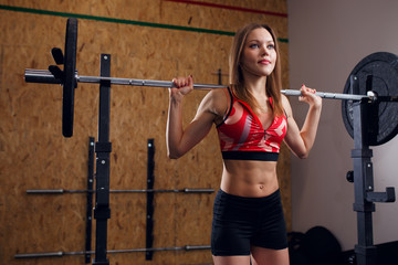 Image of sporty woman with barbell in arms