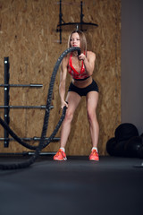 Picture of sports woman exercising with two ropes
