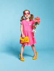 funny child girl fashionista in big mother's   shoes on colored background