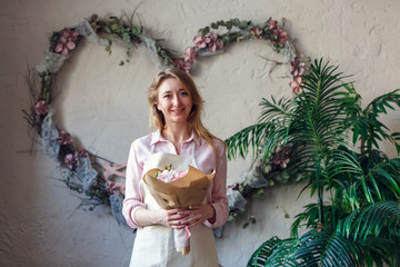Image of smiling florist with bouquet in hands