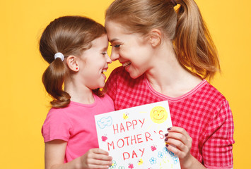 concept of mother's day. mom and child girl with postcard on colored background.