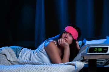 Photo of young brunette with insomnia with pink eye patch lying on bed next to clock