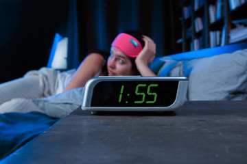 Photo of woman with insomnia with pink bandage for eyes lying on bed next to clock