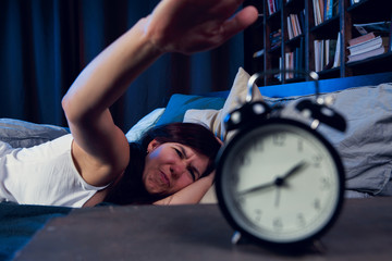 Picture of dissatisfied woman with insomnia stretching arm to alarm clock at night