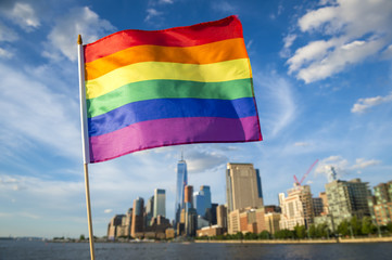 Colorful rainbow gay pride flag fluttering in the breeze against a sunny city skyline