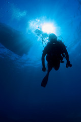 Underwater diver in back-light with his air bubbles.