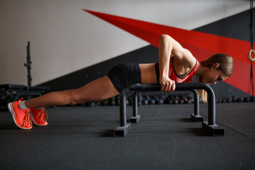 Picture side of young woman doing horizontal push-ups with bars