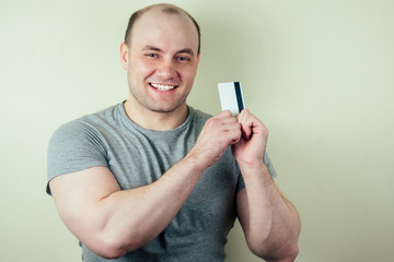 portrait of a bald man holding a credit card on a gray background. sportsman and credit card
